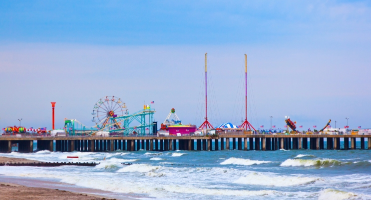 A colorful side view image of the pier in Point Pleasant Beach NJ protruding out over the water with about 10 rides on the pier including a ferris wheel with multi colored seats. Clicking on this image will bring you to the ultimate NJ beach guide