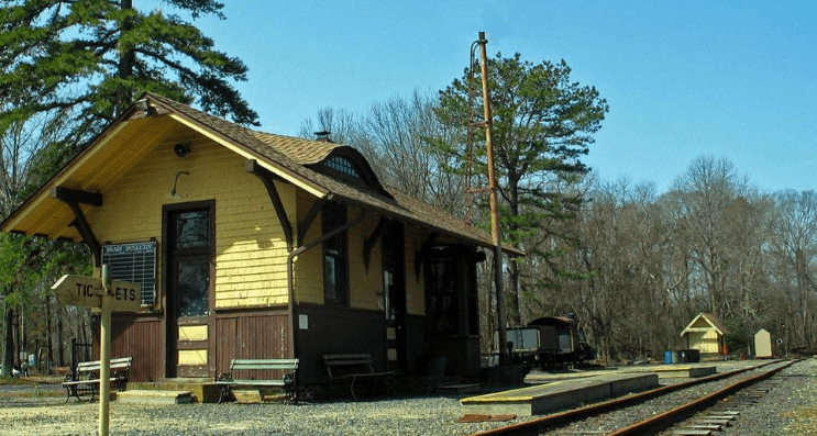 Image of a small yellow and brown outdoor ticket booth in an old train station in NJ