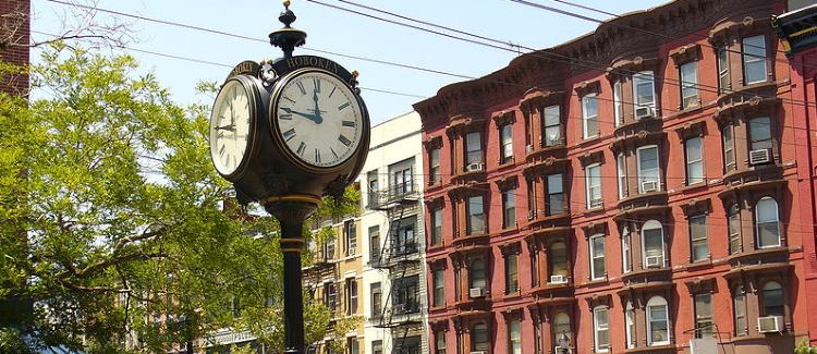 Image of a clock with red and white buildings on a beautiful downtown place to visit in Hoboken NJ