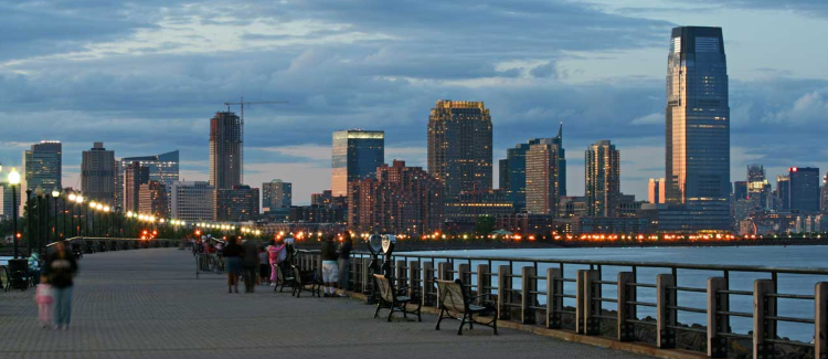 Image of the Hudson River and NYC from the Jersey City side of the river. There is a cement boardwalk with benches facing the river. It is dusk and there are a few people sitting on the far benches. The image is a symbol of one of the best places to visit in Jersey City