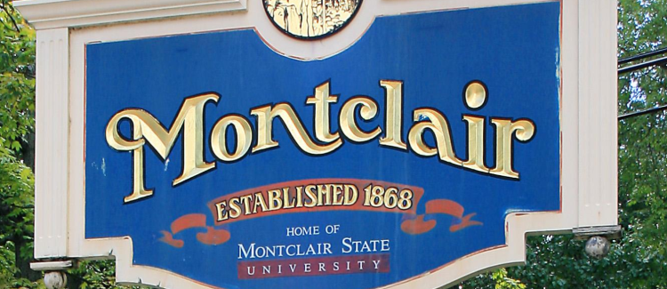 "A close-up image of a blue, orange and white ""Welcome to Montclair NJ"" sign that says ""established 1868"" and "" Home of Montclair State University"" which is a symbol to welcome visitors to find the best places to visit in Montclair"