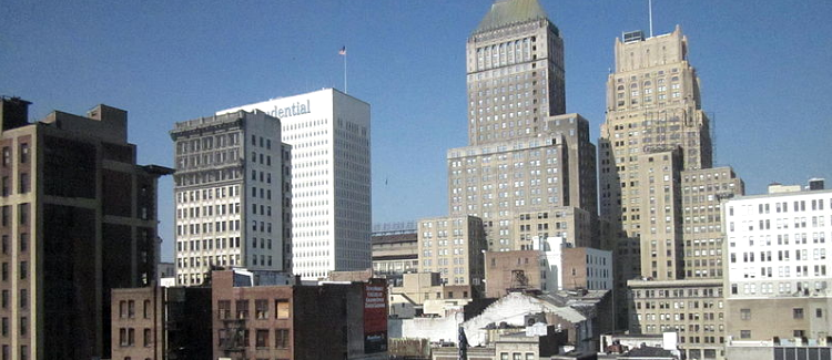A well lit up cityscape of Downtown Newark showing 12 buildings one being the white prudential center building