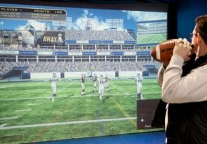 Image of a man throwing a football in the Quarterback Challenge game at Topgolf Swing Suite in iPlay America located in Freehold NJ