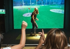 Image of woman playing golf simulator at Topgolf Swing Suite in Freehold NJ