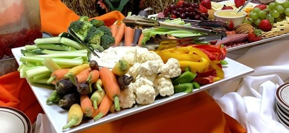 Image of a platter of vegetables on a table with an orange tablecloth including fresh sticks of celery, broccoli florets, carrots, sliced green bell peppers, green grapes and cauliflower with two different dips in the middle