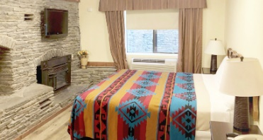 Image of the Pine Ridge Dude Ranch Santa Grande Suite guest room with a queen size bed and a New Mexican colorful blanket and fieldstone wall, fireplace and TV