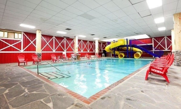 Image of the Pine Ridge Dude Ranch all-inclusive family dude ranch vacation indoor pool surrounded by a flagstone paver deck with red chairs and a yellow double water slide.