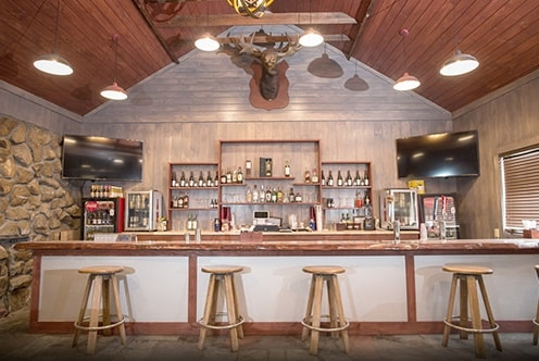 Image of the Pine Ridge Dude Ranch silver dollar bar in light tan and white colors with 4 stools and bottles of alcohol behind the bar