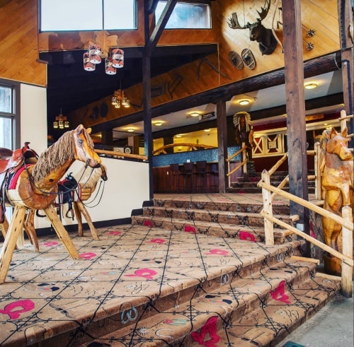 Image of the Pine Ridge Dude Ranch vacation destination just entering the ranch inside with two sets of steps and three wooden horses and a moose head on the pinewood walls in the background
