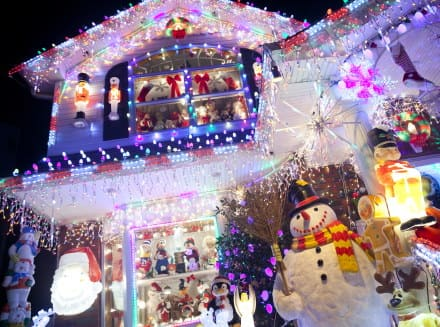 An image of a house with thousands of Christmas lights and dozens of Christmas decorations on it
